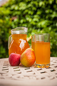 pitcher and glass of juice with an apple and a pear