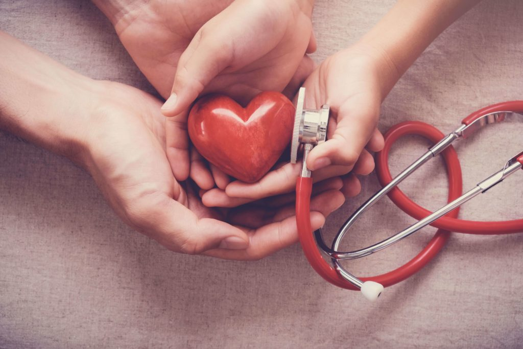 two hands holding red heart and a stethoscope
