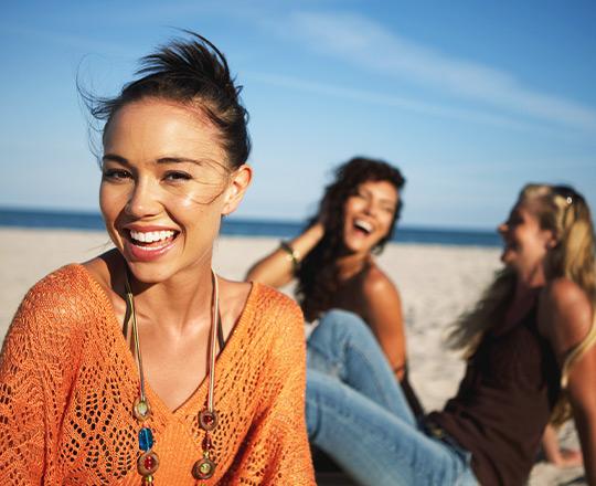 Three women laughing on the beach