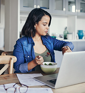Woman working remotely and eating veggies while checking the time on her watch